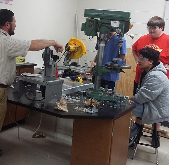 Mr. Birchfield directs students on constructing hardware.