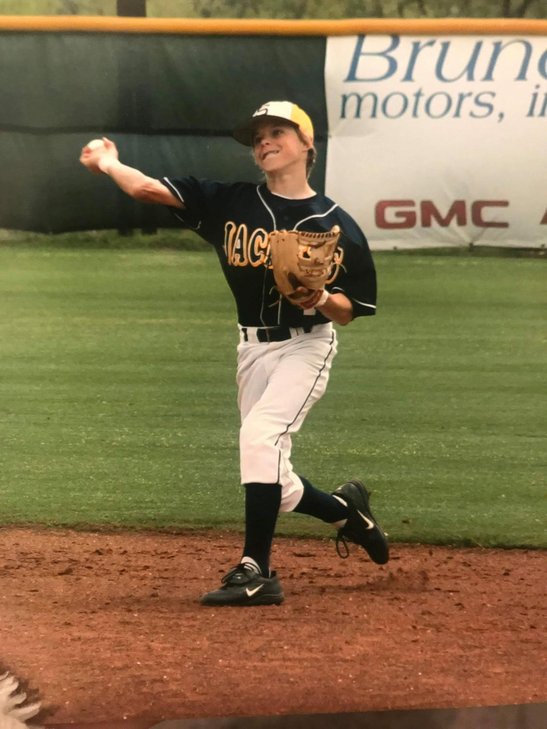 Brock Holt playing for the Stephenville Yellowjackets makes a throw across the baseball diamond while playing the infield.